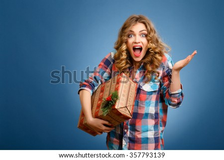 young beautiful girl with gift box in hands on blue background