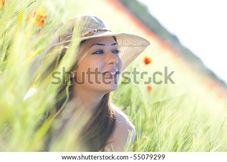 Young beautiful girl with hat staring and smiling at something - stock photo