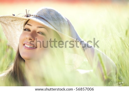 Young beautiful girl with hat staring at camera among green wheat, focus on the right eye. - stock photo