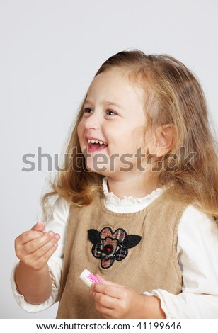 Young Beautiful Girl with lipstick in hand