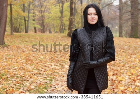 young beautiful girl with long black hair , in black quilted jacket , walking in the autumn park
