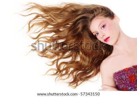 Young beautiful girl with long curly blond hair lying on white background