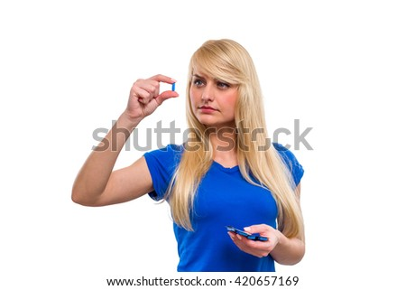 Young, beautiful girl with long hair, carefully consider the pill, isolated on a white background - stock photo