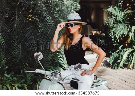 young beautiful girl with long hair in sunglasses in a black T-shirt and white pants jeans and sneakers posing on a retro scooter vintage style fashion clothing stylish woman in her red lipstick lips - stock photo