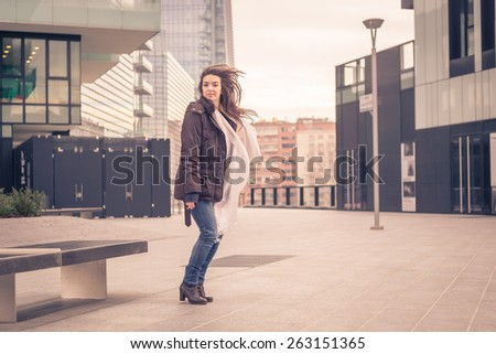 Young beautiful girl with long hair jumping in the city streets
