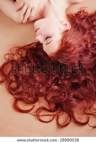 Young beautiful girl with long hair lying on the floor - stock photo