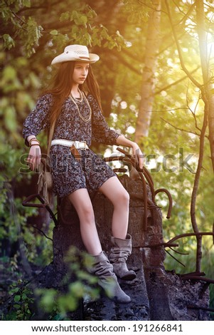 Young beautiful girl with long hair wearing a cowboy hat posing in a forest. - stock photo