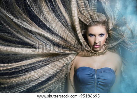 young beautiful girl with long wavy hair waving in the smoke is in the blue fone.portrait. - stock photo