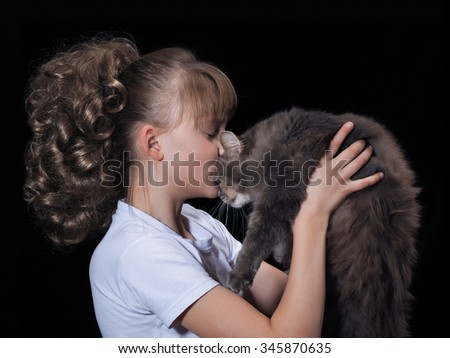 Young, beautiful girl with luxurious hair holding a gray cat. Black background - stock photo