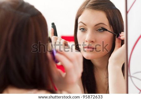 Young beautiful girl with makeup making her eyes with mascara to look sexy and gorgeous - stock photo