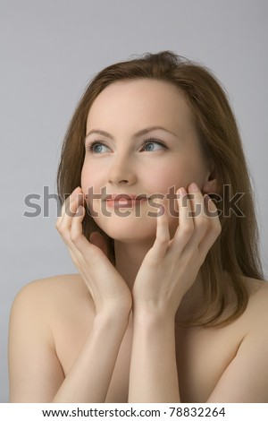 Young beautiful girl with naked shoulders, touches the face fingers. - stock photo