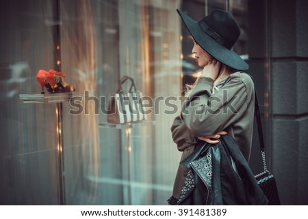 Young beautiful girl with perfect make-up, red lips, wearing a black  hat and leather coat, green shirt, looking for  glass wall of the shopping center. - stock photo