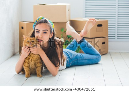 young beautiful girl with red cat, and with boxes for the move - stock photo