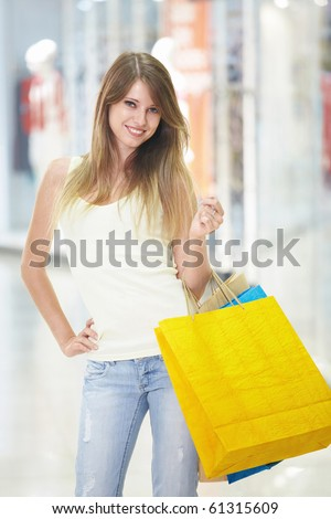 Young beautiful girl with shopping bags in store - stock photo