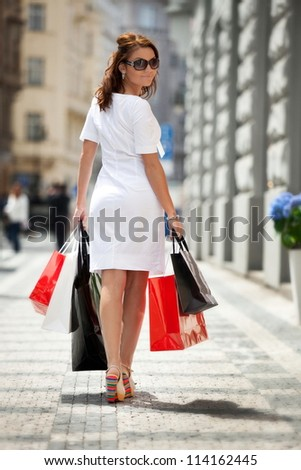 Young beautiful girl with shopping bags walking on the street in Prague. - stock photo