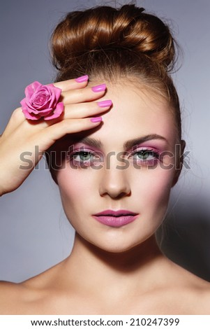 Young beautiful girl with stylish pink manicure and hair bun - stock photo