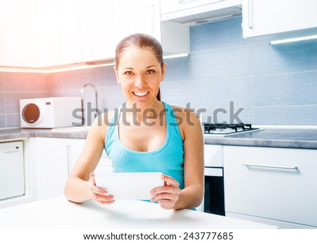 Young beautiful girl working with the tablet at home in the kitchen
