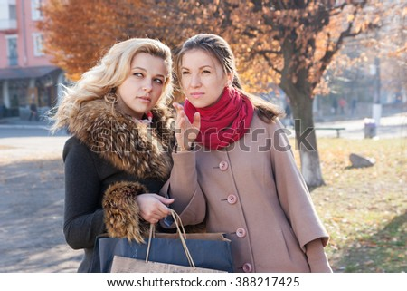 Young beautiful girlfriends with shopping bags on the small town - stock photo