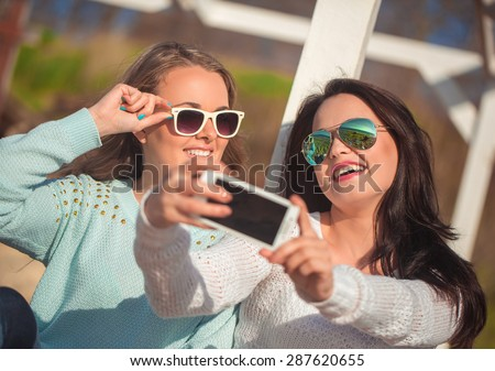Young beautiful girls taking self photo by cellphone