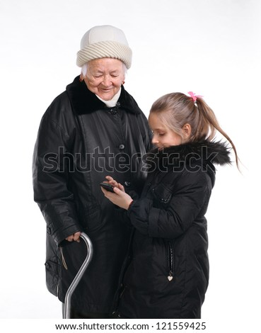 Young beautiful granddaughter showing her mobile phone to her grandmother on white background - stock photo