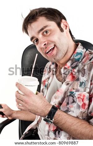 young beautiful guy white Caucasian sitting on a black chair in a colorful Hawaiian shirt and with a pleased expression on his face holding a glass of hot drink, coffee, tea, isolated over white - stock photo
