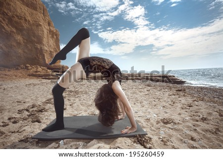 Young beautiful gymnast posing on the summer beach - stock photo
