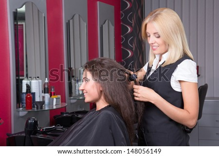 Young beautiful hairdresser at work in beauty salon - stock photo