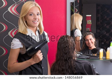 young beautiful hairdresser with hairdryer and smiling customer in beauty salon - stock photo