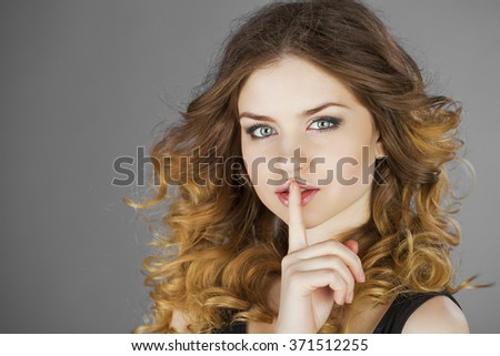 Young beautiful haired woman has put forefinger to lips as sign of silence - stock photo