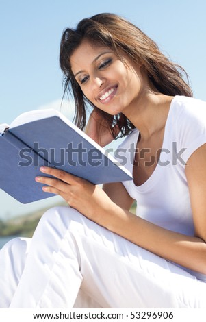young beautiful happy arabic woman reading on beach - stock photo