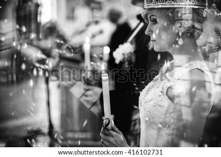 young beautiful happy couple crowned in the church - stock photo
