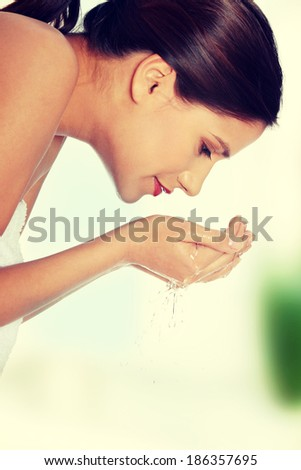 Young beautiful happy female washing her face with clear water  - stock photo