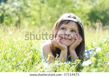 young beautiful happy girl lays on a grass - stock photo
