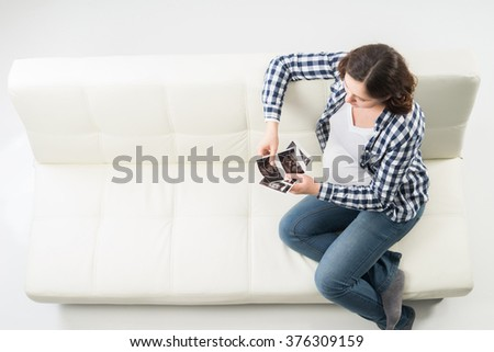 Young beautiful happy pregnant woman watching ultrasound scans. - stock photo