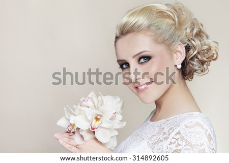 Young beautiful happy smiling bride with stylish make-up and hairdo - stock photo