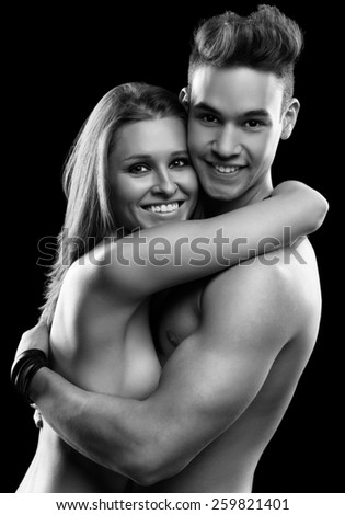 Young beautiful happy smiling couple on black - stock photo