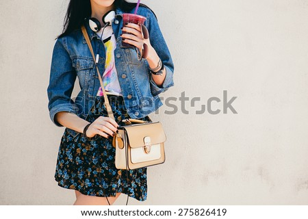 young beautiful happy stylish hipster girl, cocktail, smoozy drink, denim jacket, fashion, teen, cool accessories, purse, hat, sunglasses, vintage style outfit, wall background, headphones, close up - stock photo