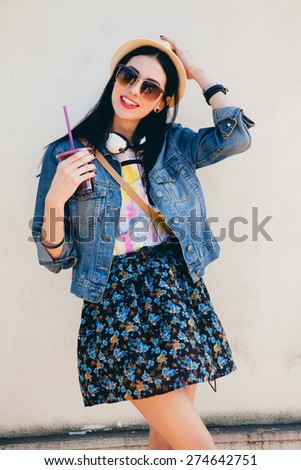 young beautiful happy stylish hipster girl, cocktail, smoozy drink, denim jacket, smiling, fashion, teen, cool accessories, purse, hat, sunglasses, amazed, vintage style, wall background, hair, wind - stock photo