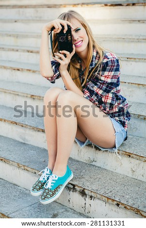 young beautiful happy stylish hipster girl, denim outfit, flirty happy, cool vintage style, having fun, sitting, stairs, oldschool film camera, take photo, hands holding, blond, smiling - stock photo
