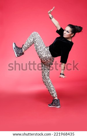 Young beautiful happy woman dancing against red background - stock photo