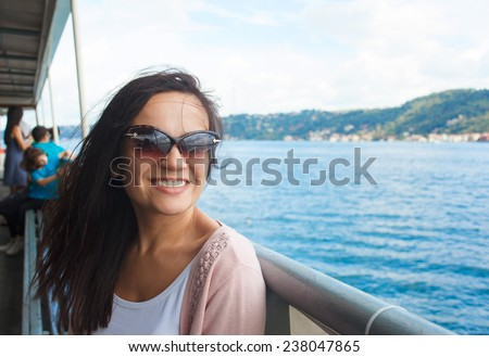 Young beautiful happy woman girl in sunglasses enjoying cruise on boat on background of Bosphorus channel in Istanbul Turkey - stock photo