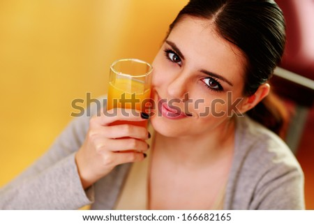 Young beautiful happy woman holding glass of orange juice at home - stock photo
