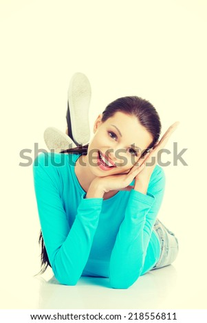 Young beautiful happy woman in casual clothes lying on floor, isolated on white - stock photo