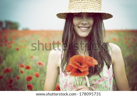Young beautiful happy woman in straw hat on a poppy field, summer outdoor. - stock photo