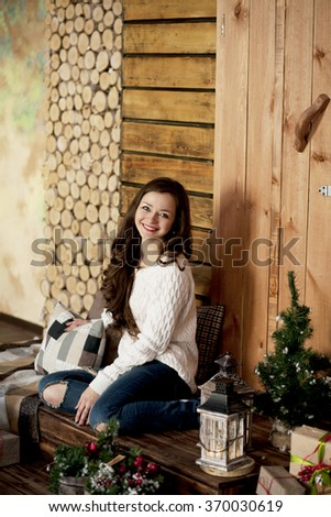 Young beautiful happy woman in sweater and blue jeans sitting on floor at home - stock photo