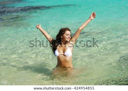 Young beautiful happy woman playing in blue water on a sunny day. Pretty girl enjoying vacation, sun and sea. - stock photo