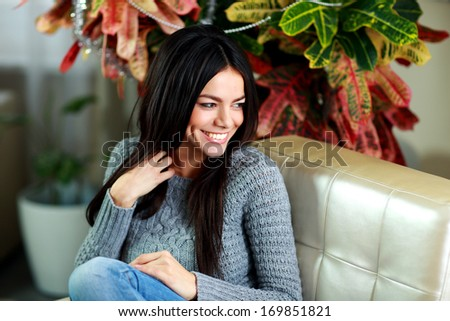 Young beautiful happy woman sitting on the armchair and looking away at home - stock photo