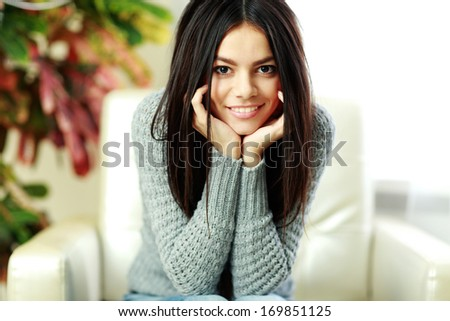 Young beautiful happy woman sitting on the armchair at home - stock photo
