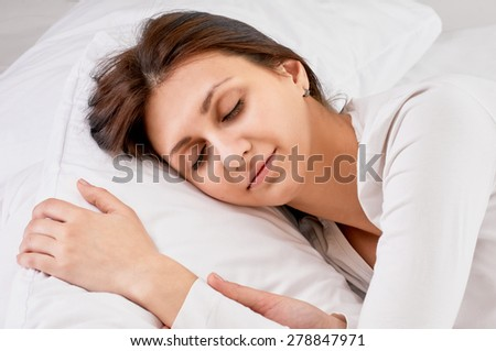 Young beautiful happy woman sleeps on bed, close up - stock photo