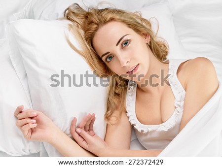 Young beautiful happy woman waking up on bed - stock photo